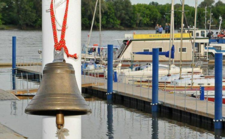 Zdjęcie przedstawia przystań z dzwonem marynarskim na pierwszym planie