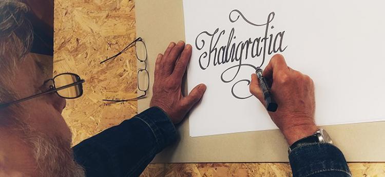 """Pan Zbyszek piszący słowo """"kaligrafia"""""""